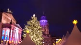 Gendarmenmarkt Christmas market kiosks in Berlin illuminated at night, Germany, showing christmas tree closer