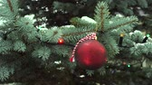 Christmas red ball hanging on evergreen tree with glowing garland, falling snow in background Vídeos