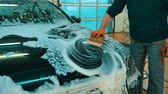 garagem : Man worker washing luxury car on a car wash