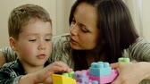 inşaat : Happy young mother with her son on a sofa playing with building kit Stok Video