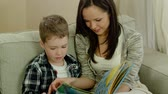 мама : Mother with her son on a sofa in home interior reading book Стоковые видеозаписи
