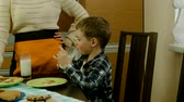 food and drink : Young happy mother and her child eating healthy breakfast Stock Footage