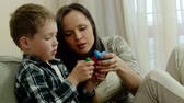 мама : Happy young mother with her son on a sofa playing with building kit Стоковые видеозаписи