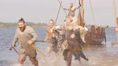 ship : Mad vikings warriors in the attack, running along the shore with Drakkar on the background