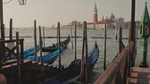 набережная : Parked gondolas on Piazza San Marco and The Doges Palace embankment with the bell tower of the Saint Giorgio Maggiore Church on background. Стоковые видеозаписи