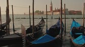 canal : Parked gondolas on Piazza San Marco and The Doges Palace embankment with the bell tower of the Saint Giorgio Maggiore Church on background. Stock Footage