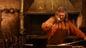 glow : Senior blacksmith forging the molten metal on the anvil in smithy