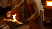 trabalho manual : The blacksmith with brush handles the molten metal on the anvil in smithy Stock Footage