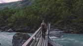 suspensão : Aerial view of a woman hiker walking on the suspension bridge over wild mountain river.