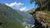 escandinavo : Woman hiker enjoying scenic landscapes at a cliff edge, Geirangerfjord, Norway Stock Footage