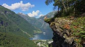 noruega : Woman hiker enjoying scenic landscapes at a cliff edge, Geirangerfjord, Norway Stock Footage