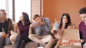 colega : Group of multi ethnic young friends eating pizza in home interior