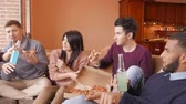 étel : Group of multi ethnic young friends eating pizza in home interior