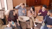 многонациональная : Group of multi ethnic young friends eating pizza in home interior