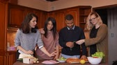 многонациональная : Group of multi ethnic young friends in kitchen prepare for party