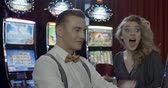 jogos de azar : Couple playing slot machine in a casino