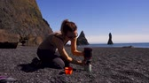 vulcão : Woman making hot drink on Reynisfjara beach near Vik, Icealnd Stock Footage