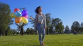 jumping : Happy girl with rainbow-colored air balloons in a park.