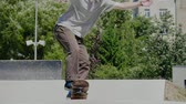 Young skater doing tricks outdoors. Slowmotion video 150fps