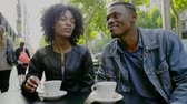 beijos : Young happy black couple drinking coffee in street cafe