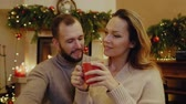 Couple with a cup of hot drink at Christmas time Стоковые видеозаписи