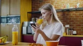 utilização : Woman eats breakfast and uses her mobile phone Stock Footage