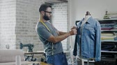 портниха : Fashion designer working in his studio Стоковые видеозаписи