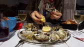 molusco : Close-up shot of women pouring lemon juice on the open oysters Stock Footage