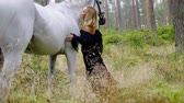 outdoor pursuit : Beautiful woman in evening dress hugging with a horse in forest