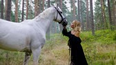 animais selvagens : Beautiful woman in evening dress hugging with a horse in forest