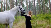 törekvés : Beautiful woman in evening dress hugging with a horse in forest