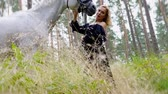 attention : Beautiful woman in evening dress hugging with a horse in forest