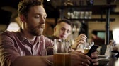 addio al celibato : Man with a mobile phone drinking draft beer in a pub
