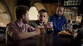 друзья : Cheerful friends drinking draft beer and eating snacks in a pub