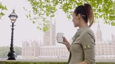 theems : Woman drinking coffee against House of Parliament in London