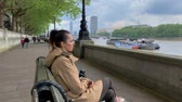 theems : Woman seating near Thames river time-lapse Stockvideo