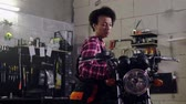 механик : African american woman mechanic repairing a motorcycle in a workshop Стоковые видеозаписи