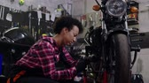 обычай : African american woman mechanic repairing a motorcycle in a workshop Стоковые видеозаписи