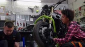 механик : Mechanic and his helper repairing a motorcycle in a workshop