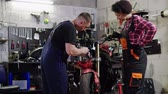 炭水化物 : Mechanic and his helper repairing a motorcycle in a workshop