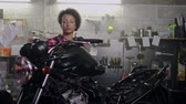 炭水化物 : African american woman mechanic repairing a motorcycle in a workshop 動画素材