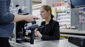 munkatársai : Pregnant woman paying with smartphone goods in a grocery store Stock mozgókép