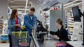 munkatársai : Young couple buying goods in a grocery store