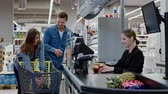 verkoopster : Young couple buying goods in a grocery store