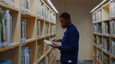 mnohonárodnostní : Young black man choosing book in public library