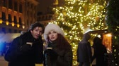 Couple drinking hot drinks on a cold winter evening outdoor Stok Video