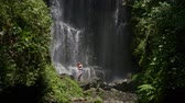 deštivý : Woman near Labuhan Kebo Waterfall located in Munduk, Bali