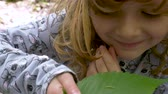 housenka : A smiling little girl hold a leaf with a tiny green caterpillar crawling on it, and looks at the camera. Close up. Dostupné videozáznamy