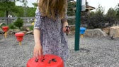 seixos : A child digs out wet rocks with her hands and places them on a red stool in an outdoor playground. Long shot. Stock Footage