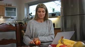 čtyřicátá léta : A woman working at home on her computer takes a break and bites into an apple. She looks at the camera happily. Dostupné videozáznamy